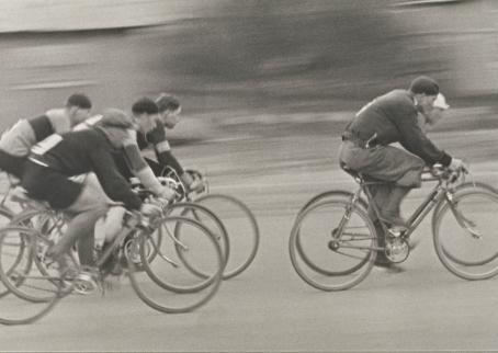 Mustavalkoisessa kuvassa monta henkilöä polkee pyörällä. Tausta on epätarkka.