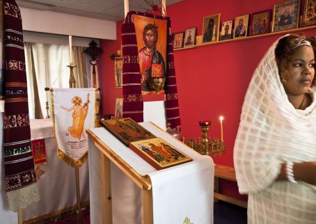 Punaseinäisessä huoneessa on paljon uskonnollisia esineitä ja ikoneita. Oikeassa reunassa on nainen valkoinen huivi päällään.