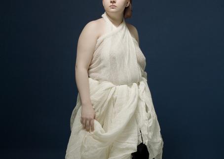 Sinistä taustaa vasten nainen, jolla on päällään pienireikäisestä kankaasta tehty mekko.