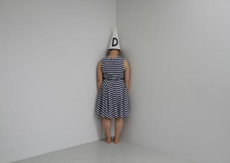 Valkoisen huoneen nurkassa seisoo selin raitamekkoinen nainen. Hänellä on päässään valkoinen kartionmuotoinen hattu, jossa on mustalla kirjain D.