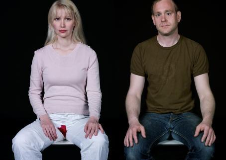 Mustaa taustaa vasten istuu vierekkäin mies ja nainen. Naisella on valkoiset housut ja hänellä on haarovälissä punainen tahra.