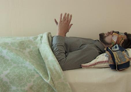 Mies makaa sängyssä kauluspaita päällä. Hänen päällään on viltti vedettynä vatsaan asti. Kädet ovat nostettuna ylös, ja silmien päällä on huivi.