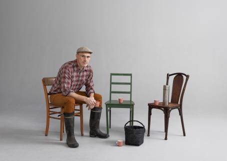 Mies istuu tuolissa kumisaappaat jalassa ja muki kädessään. Hänen vieressään on kaksi tuolia, joilla on mukit ja termospullo. Maassa on kori.
