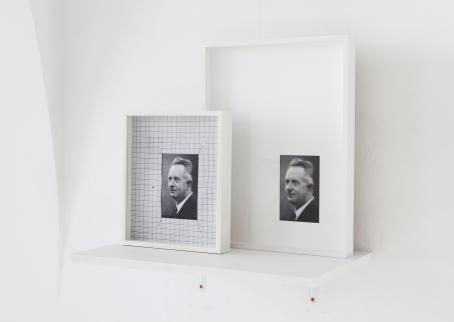 Valkoista taustaa vasten, valkoisella hyllyllä kaksi erikokoista valkoista kehystä joissa molemmissa on sama pieni mustavalkoinen kuva. Isommassa kehyksessä kuva on pikselöitynyt, mutta pienemmässä se on tarkka.