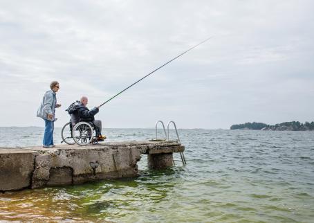 Vanha mies pyörätuolissa on onkimassa kivisellä laiturilla. Hänen vieressään on vanha nainen.