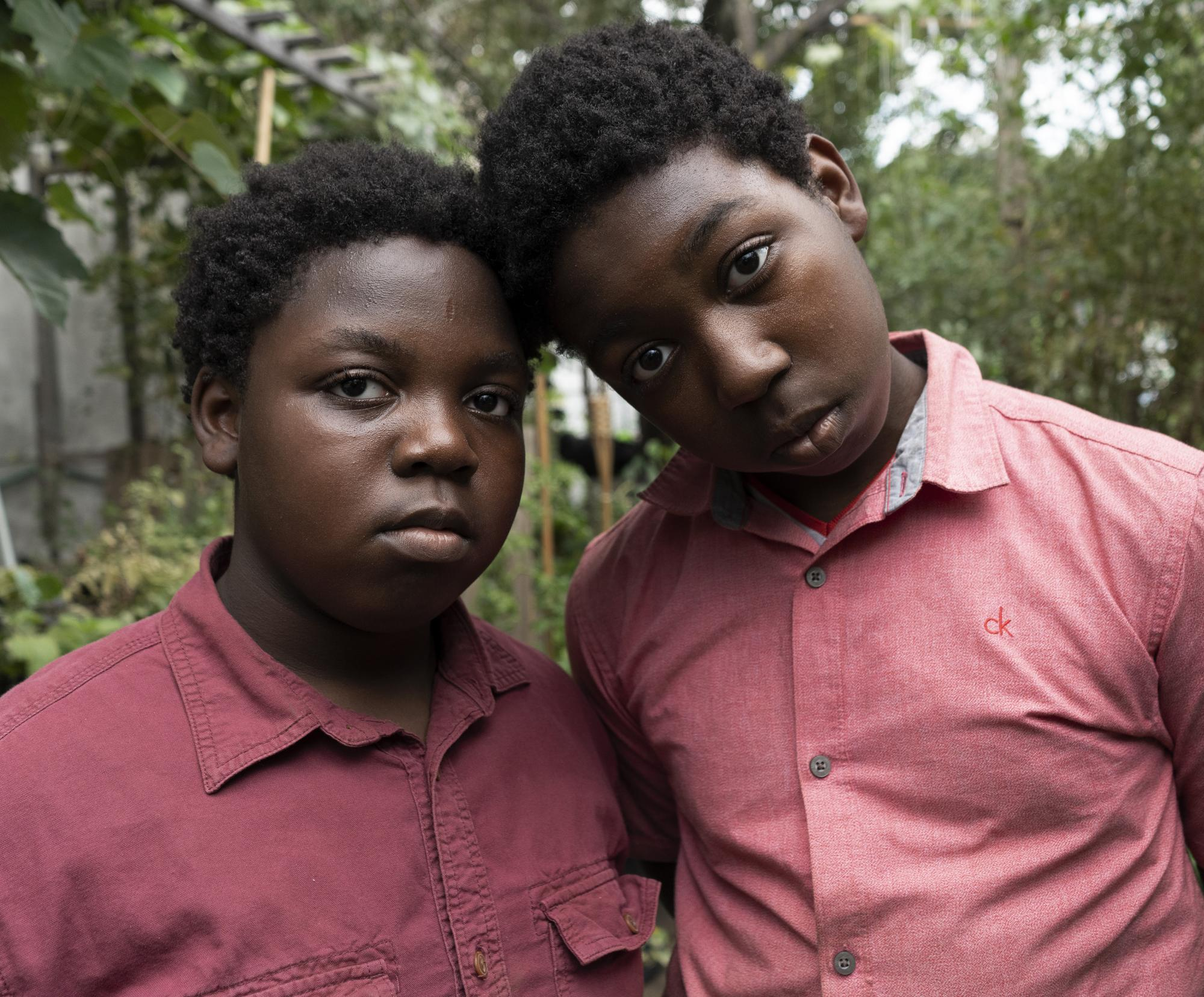 Two black children. Other is a bit taller, and is leaning on the other's head. Both have a light red collared shirt and both are looking straight into the camera.