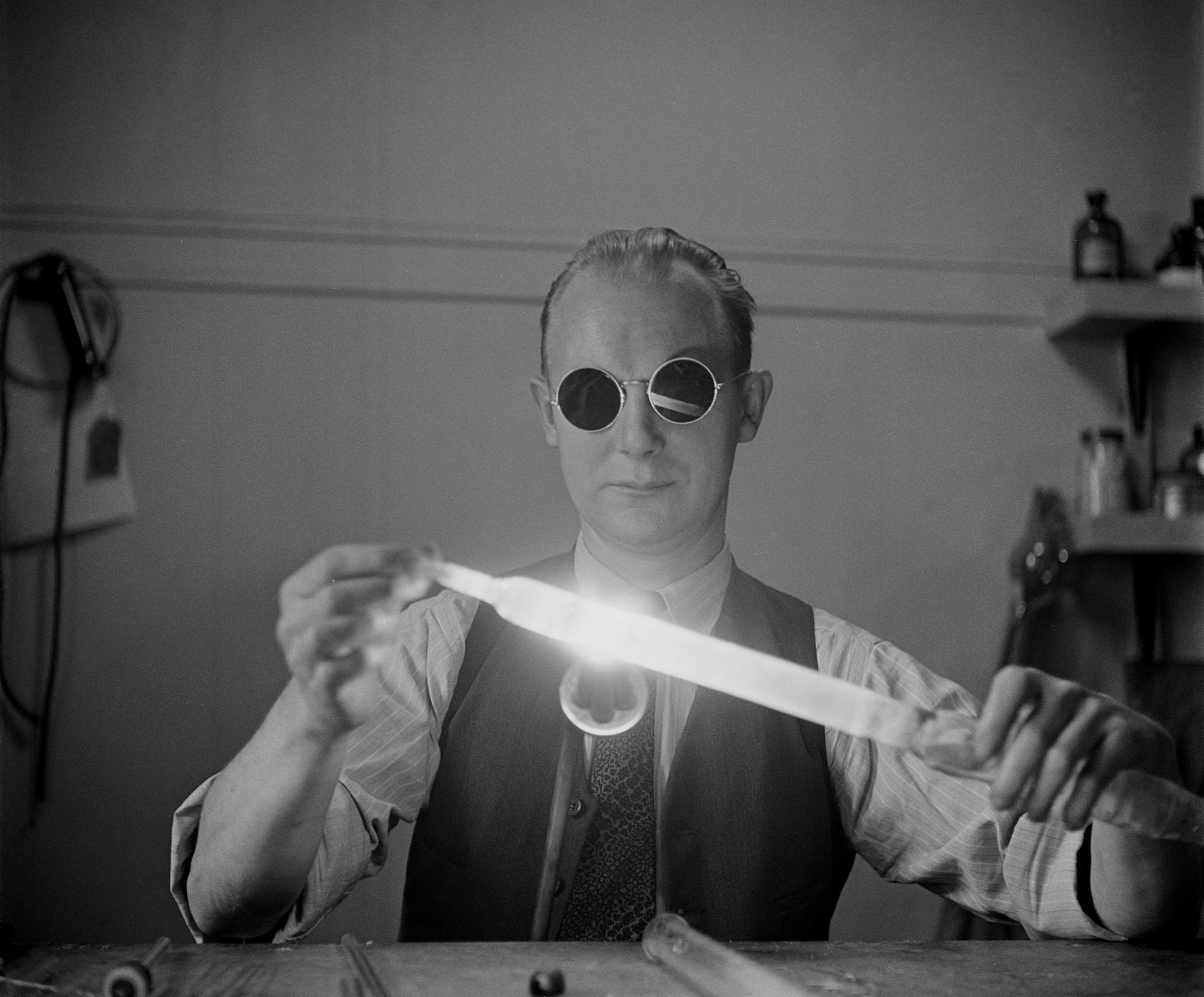 In a black and white photo a man is sitting at a desk and holding a glowing tube. He is wearing dark, round glasses.